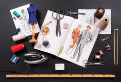 Selection of tools for a tailor or seamstress. With retro patterns, iron, scissors, tape measure, yarn, needles and a ruler displayed on a black background royalty free stock image