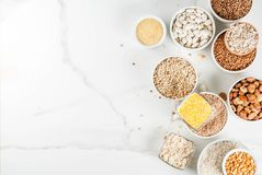 Various types cereal grains groats. Selection various types cereal grains groats  in different bowl on white marble background, above copy space Royalty Free Stock Photos