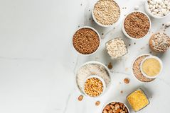 Various types cereal grains groats. Selection various types cereal grains groats  in different bowl on white marble background, copy space above Royalty Free Stock Photography