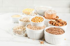 Various types cereal grains groats. Selection various types cereal grains groats  in different bowl on white marble background, copy space Royalty Free Stock Photography