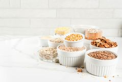 Various types cereal grains groats. Selection various types cereal grains groats  in different bowl on white marble background, copy space Stock Photos