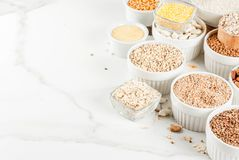 Various types cereal grains groats. Selection various types cereal grains groats  in different bowl on white marble background,  space for text Royalty Free Stock Photo