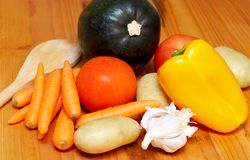 Selection of vegetables. Carrots, squash pumpkin, tomatoes, potatoes, peppers and garlic on the kitchen worktop Stock Images