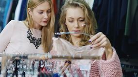 Selection of women`s clothing. Two friends looking at the stand with underwear. A pleasant shopping, intimate underwear stock footage