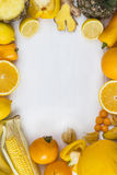 Yellow fruit portrait frame. Selection of yellow and orange fruit and vegetables on a table Royalty Free Stock Photo