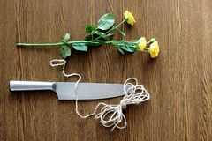 Selection. Yellow rose and a knife on a wooden table. Photography has two meanings. The first - the thread and a knife - these are the things to pack flowers Royalty Free Stock Photos