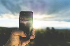 Selective closeup shot of a person holding a black phone taking a picture of the sunset