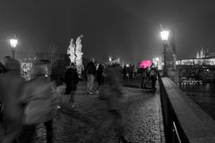 A selective colour scene of tourists dashing about in the snow,