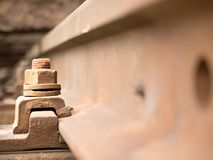Selective field of focus. Detail of rusty screws and nut on old railroad track. Concrete tie Stock Photography
