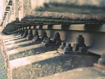 Selective field of focus. Detail of rusty screws and nut on old railroad track. Concrete tie Royalty Free Stock Image