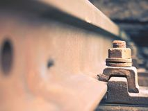 Selective field of focus. Detail of rusty screws and nut on old railroad track. Concrete tie Royalty Free Stock Images