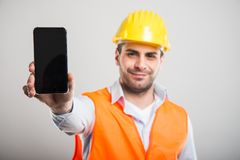 Selective focus of architect holding black screen smartphone. And smiling on gray background Stock Photos