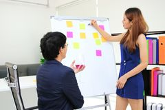 Selective focus on Asian executive boss listening employee explaining strategies on flip chart in boardroom stock images