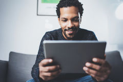 Selective focus.Attractive bearded African man using tablet while sitting on sofa in his modern office.Concept of young. Selective focus.Attractive bearded Royalty Free Stock Photos