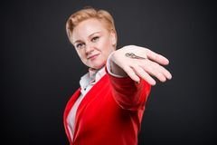 Selective focus of attractive business woman showing house key. On black background Royalty Free Stock Image