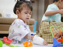 Baby patient playing toys with her family members. Selective focus of baby patient playing toys with her family members - playing with baby at a hospital to help royalty free stock photography