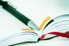 Selective focus of ball pen on opened lined diary book with cale Stock Photo