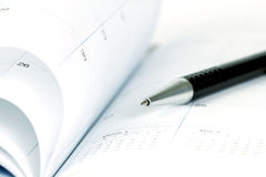 Selective focus of ball pen on opened lined diary book with cale Royalty Free Stock Photo