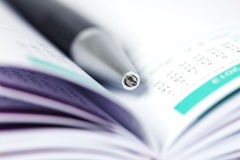 Selective focus of ball pen on opened lined diary book with cale Royalty Free Stock Images