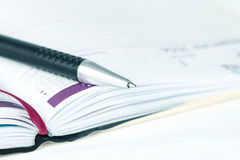 Selective focus of ball pen on opened lined diary book with cale Stock Photos