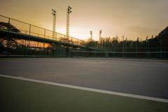 Selective focus on the baseline of tennis court with sunset sky background. Landscape of sport place. royalty free stock photo