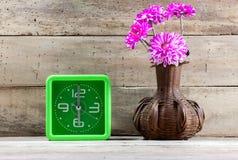 Selective focus beautiful pink flower in jar wood ,green clock. Stock Photography