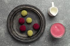 Selective focus on beetroot latte healthy coffee alternative, matcha green tea and pink raspberry beetroot truffles. Close up, gray background, copy space royalty free stock images