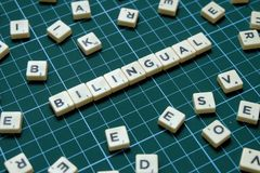 Selective focus of Bilingual word on square green mat background stock images