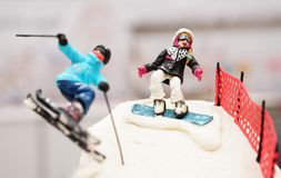 Selective focus of a birthday cake in which skier couples skiing. Downhill in high mountain Royalty Free Stock Photography