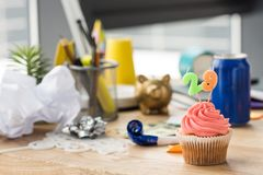 selective focus of birthday cupcake and party decorations at workplace royalty free stock image