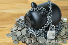 Selective focus on black piggy bank with chains and lock pad and stock photos