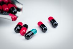 Selective focus blue-green capsule pill and drug tray with red-black capsule. Global healthcare. Antibiotics drug resistance. Antimicrobial capsule pills stock photo