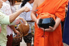 Selective focus on bowl. Thai people put food to a Buddhist monk`s alms bowl in Songkran festival Day Stock Photography