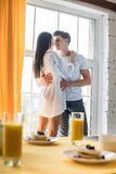 Selective focus of breakfast on table and multicultural couple in love hugging. At home royalty free stock images
