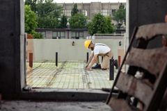 Selective focus of builder in protective googles and hardhat working. At construction site stock photos