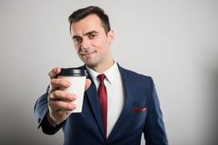 Selective focus of business man offering takeaway coffee. On gray background Stock Photography