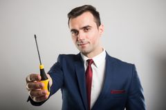 Selective focus of business man showing one screwdriver. On gray background Stock Photos