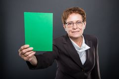 Selective focus of business senior lady holding green cardboard. On black background with copsyapce advertising area Stock Photo