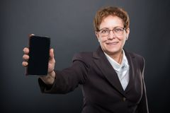 Selective focus of business senior lady showing smartphone. On black background Stock Image