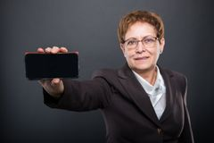 Selective focus of business senior lady showing smartphone. On black background Royalty Free Stock Photos