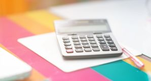 Selective focus calculator and pink pen beside on computer mouse stock photos