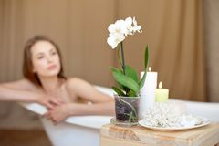 Selective focus of candles and flowers on the wooden table in spa salon with blurred woman on background. royalty free stock photos