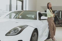 Elegant young woman buying new car at dealership stock images