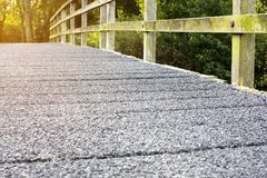Selective focus of cement bridge with wooden rack walkway along to the forest Stock Images