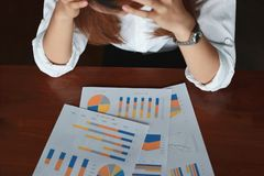 Selective focus on charts on the workplace with upset stressed Asian business woman. Selective focus on charts on the workplace with upset stressed Asian Royalty Free Stock Image