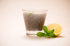 Selective focus of chia seeds drink with water in transparent gl. Ass with lemon balm Royalty Free Stock Photography