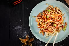 Selective focus on Chinese noodles with chicken and vegetables on dark background. stock photography