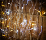 Selective focus of Christmas warm gold garland lights on wooden rustic background. filtered image Royalty Free Stock Image