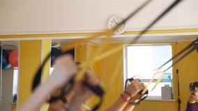 Selective focus on clocks while fitness training. Selective focus on the clock on the wall while people having fitness training. Woman doing exercises with TRX stock video footage