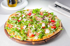 Selective focus Close up Delicious Pizza with hamon and cherry tomato slices, parmezan cheese and arugula on the wooden board Royalty Free Stock Photo